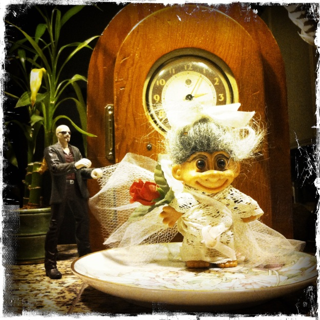 Grandma made a dress for the troll doll out of doily and ribbon.  She then arranged the doll with the figurine in front of the clock.